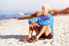 Man in sports wear sitting at the beach Stock Photography