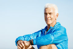 Man in sports wear sitting at the beach Royalty Free Stock Photography