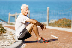 Man in sports wear sitting at the beach Stock Image