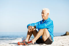 Man in sports wear sitting at the beach Royalty Free Stock Image