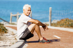 Man in sports wear sitting at the beach Stock Photo