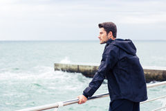 Man in sports wear standing near sea Stock Photos