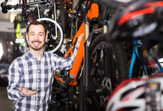 Man in sports workshop mounts bike using special tools Royalty Free Stock Images