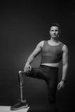 Man sportsman athlete posing, prosthetic leg. One young adult man disabled, sportsman athlete posing, one prosthetic leg, standing, black and white Stock Photography