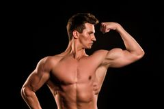 Man sportsman flex arm with fist. Bodybuilder show muscles, biceps and triceps. Athlete with bare torso, six pack, ab on black background. Sport, bodybuilding Royalty Free Stock Photos