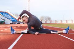 A man sportsman performs a transverse twine, on the athletics track of the stadium. stock photos