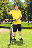 Man in sportswear giving thumb up next to his bike in a park Royalty Free Stock Photography