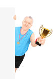 Man in sportswear holding a gold cup behind blank panel Stock Photo