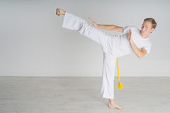 Man in sportswear performing a kick. Young Man in white sportswear performing a kick. Indoor martial arts training, capoeira Royalty Free Stock Image