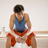 Man in sportswear relaxing after work out. Fatigued man in sportswear relaxing after work out Stock Images