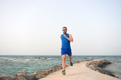 Man in sportswear running on sea coast. future success. successful runner. summer activity. sport recreation. healthy. Lifestyle. run for success. Towards royalty free stock image