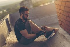 Man tying shoelaces before workout. Man in a sportswear sitting on a building rooftop terrace, tying shoelaces before workout Stock Photo