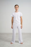 Man in sportswear standing in a white room, the portrait in full growth. Royalty Free Stock Image