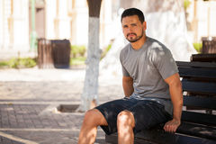 Man in sporty outfit sitting on a park bench Stock Photo