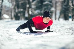 Man in sporty wear alone working out on a winter day. Young man in sporty wear alone working out on a winter day stock photos