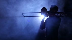 Man in spotlight in smoky studio plays on trombone, silhouette. Man in spotlight in smoky studio plays on trombone, dark silhouette of man in smoke is visible to stock video