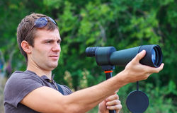 Man with spotting scope looks at the target. Stock Images