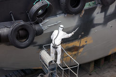 Man spray painting hood of ship. Grey in dock Royalty Free Stock Photography