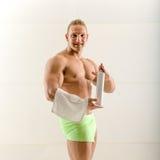 Man spraying deodorant under his arm Stock Images