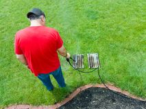 Man spraying a dirty BBQ grill with a power hose royalty free stock photography