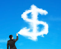 Man spraying dollar sign shape cloud paint with blue sky. Background royalty free stock photography