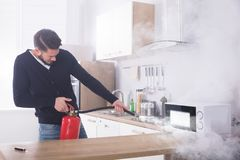 Man Spraying Fire Extinguisher On Microwave Oven. Young Man Spraying Fire Extinguisher On Microwave Oven In The Kitchen royalty free stock image