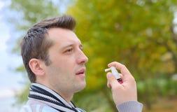 Man spraying with nasal spray Stock Image