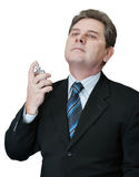 Man spraying perfume cologne to his neck. On a white background Stock Image