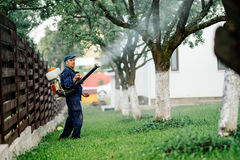 Man spraying toxic pesticides and herbicides in fruit orchard. Using automatic sprayer royalty free stock photos