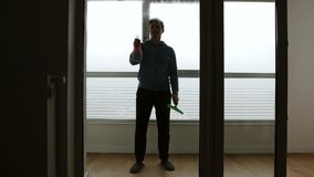 Man sprays window cleaner on large window and washes it in the day - Front View stock video
