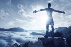 Man on a summit over an ocean of clouds. Man with spread arms on top of mountain overlooking a valley full of clouds Stock Images