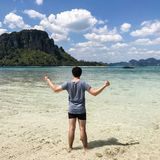 Man spread his hands on beach. Man on beach hold hands arms up, rear man spread his hands on beach. Man on beach. Back view of Young man spread his hands on Royalty Free Stock Photo