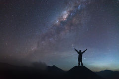 Man is spreading hand on hill and seeing the Milky Way Royalty Free Stock Image