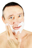 Man spreads shaving foam on his cheeks. Over white background Stock Photography