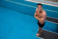 Man Standing On Diving Board At Public Swimming Pool Stock