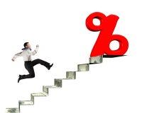 Man spring in mot procentsatstecken överst av pengartrappa Royaltyfri Fotografi