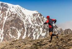 Man spring på en lantlig väg under solnedgång i bergen Royaltyfria Bilder