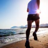 Man spring på solnedgången på en sandig strand i en solig dag Royaltyfri Fotografi