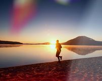 Man spring på stranden mot bakgrunden av en härlig solnedgång Sand av bergsjön Arkivbild