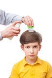 Man is sprinkling child head by anti-nits spray Royalty Free Stock Images