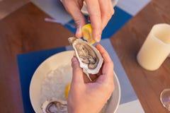 Man sprinkling some lemon juice on fresh oysters. Lemon juice. Mature prosperous man sprinkling some lemon juice on fresh oysters while relaxing on summer Stock Photo