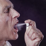 Man spritzing medication into mouth stock image