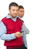 Man spying friend with phone Stock Photography