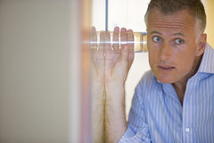 Man spying by listening through wall with glass Stock Images