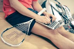 Man with squash racket and laptop Royalty Free Stock Photo