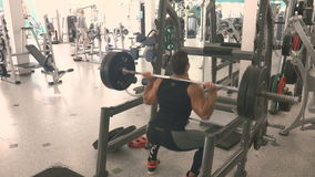 A man squats with a barbell on shoulders in gym stock video footage
