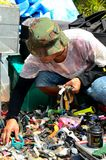 Man squats and examines watches at second hand market. Singapore - October 20, 2013: A man wearing a camouflaged cloth cap squats while rummaging through a pile Stock Image
