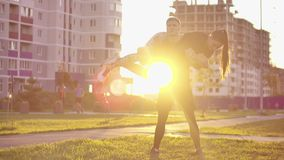 A man squats with a girl sitting on his shoulders in a city Park against a backdrop of buildings at sunset in slow. Motion stock video