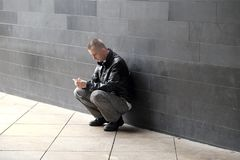 Man looking at his mobile phone. Man squatting against a bare wall texting on his mobile phone Stock Photo