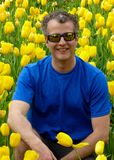 A man squatting down in front of a yellow tulips gardrn Royalty Free Stock Image